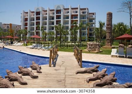 Crocodile statues flank a wooden bridge in an El Salvador resort
