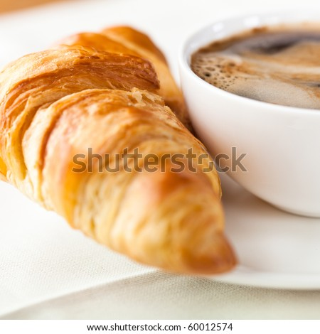 Croissant and a cup of delicious coffee - stock photo