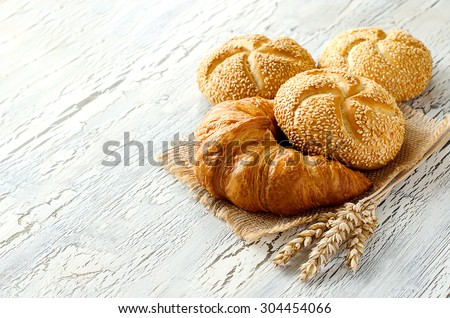 Croissant and small loaf with sesame, ears of wheat, baked bread on sackcloth, bakery concept, copy space white background
