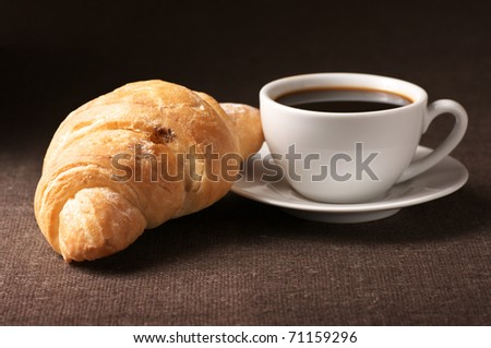 Croissant and white cup of black coffee on brown canvas.