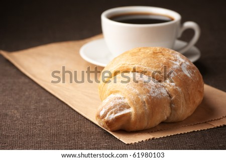 Croissant and white cup of black coffee on paper bag.