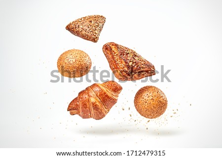 Croissant bun brioche cake flying in air. Fresh baked cookie with sesame, sunflower seed falling on white. Delicious french grain baking. Levitation, fly bread bakery products cafe concept