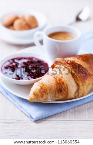 Croissant, cherry marmalade and a cup of coffee on a plate