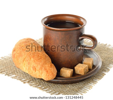 Croissant in a cup of coffee on a white background