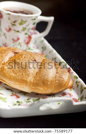 croissant on the plate with tea cup