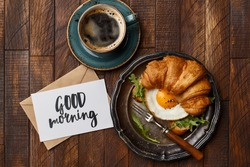 Croissant sandwich with fried egg and arugula, cup of coffee and greeting card