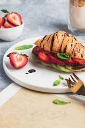 croissant sandwich with kiwi, strawberry, mint, chocolate sauce and dalonga coffee. breakfast concept. food delivery. top view with copyspace