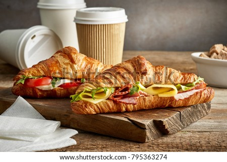 croissant sandwiches and coffee cups on wooden table