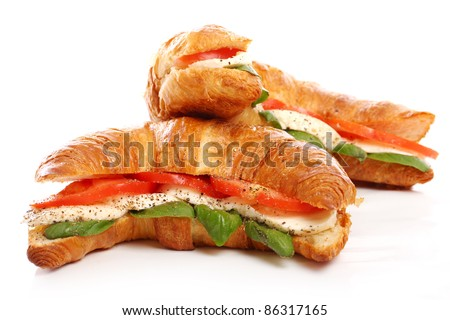 Croissant with basil, tomato and mozzarella over white background