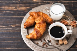 Croissant with chocolate hazelnut spread and cup of coffee on a metal vintage tray. Continental breakfast with flowers on dark wooden table