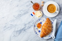 Croissant with coffee, jam, butter and French flag. Continental breakfast concept. Copy space. Top view.
