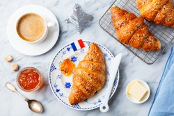 Croissant with coffee, jam, butter and French flag. Continental breakfast concept. Top view.