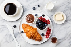 Croissant  with fresh berries, chocolate spread and butter with cup of coffee on a marble texture background. Top view