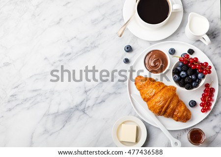 Croissant  with fresh berries, chocolate spread and butter with cup of coffee on a marble texture background. Top view Copy space