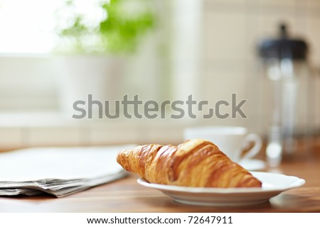 Croissant with newspaper and a cup of coffee on a kitchen counter