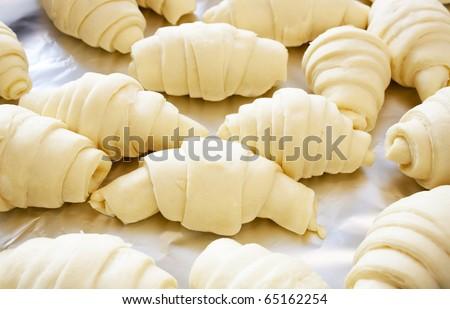 Croissants on aluminum foil prepared for baking - stock photo