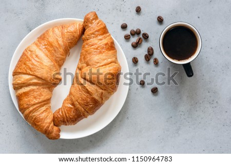 Croissants with coffee. Two french croissants on plate and cup of espresso coffee on concrete background, top view