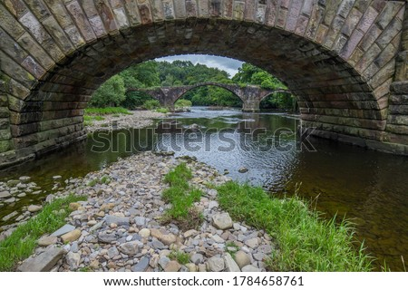 Cromwells bridge in the Ribble Valley, Lancashire. Old stone bridge over the river Hodder shot through an arch of the newer lower Hodder bridge.