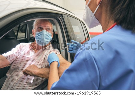 Crop anonymous nurse inoculating senior male driver in sterile mask with injector during COVID 19 pandemic