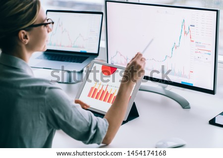 Crop back view of modern woman accounting statistical data while exploring charts on monitor of computer working at desk in office