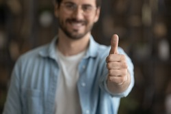 Crop close up blurred view of happy male client or customer show thumb up recommend good quality service or company. Smiling man feel satisfied pleased give recommendation. Review concept.