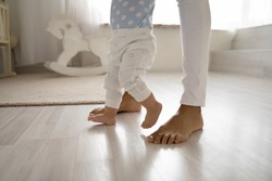 Crop close up of biracial little toddler infant make first steps on home floor hold loving mother hands. Small African American baby child learn walking with mom support care. Childcare concept.