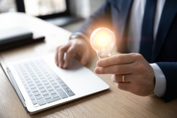 Crop close up of businessman sit at desk hold light bulb inspired by innovative business idea, male boss or director motivated with successful startup in office, innovation, energy save concept