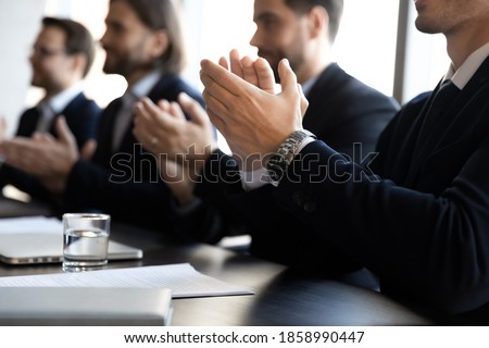 Crop close up of businessmen in formal suit sit ta desk in office applaud for presentation. Male employees businesspeople clap hands feel thankful for training. Appreciation, acknowledgment concept. Foto d'archivio ©