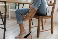 Crop close up of businesswoman sit at desk in office take off uncomfortable heels shoes suffer from legs pain ache. Female employee touch massage feet, feel discomfort in foot, have strained muscles.