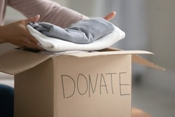 Crop close up of caring female volunteer put gather clothes in box make donation to needy people. Woman stack apparel things in package donate to poor, those in need. Reuse, recycle, charity concept.