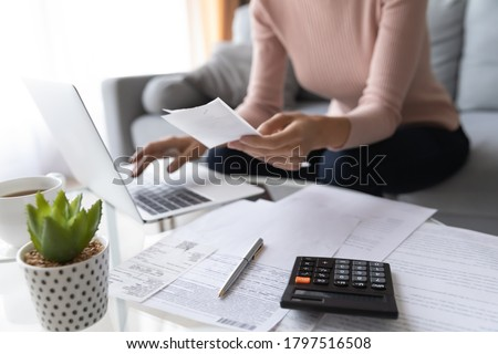 Crop close up of economical woman work on laptop at home pay bills taxes on gadget online, provident female calculate finances expenditures on machine, manage plan family household budget on computer