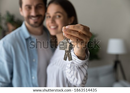 Crop close up of excited young Caucasian couple show keys to new shared home or dwelling. Happy man and woman spouses feel overjoyed moving relocating to own house. Rental, real estate concept. Stockfoto ©