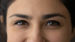 Crop close up of eyes of smiling young Indian woman look at camera feel optimistic satisfied. Closeup of happy millennial mixed race ethnicity female. Diversity, ethnic, wide view concept.