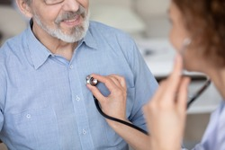 Crop close up of female doctor hold stethoscope listen to mature male patient heartbeat in private clinic. Woman nurse or GP use phonendoscope in hospital check mature man heart rate at consultation.