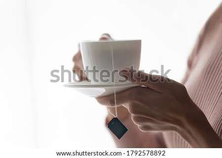 Crop close up of female hands hold white porcelain mug with bag inside, drink hot black green tea at home. Woman client enjoy warm brew or beverage in cup, relax rest having break indoors Photo stock ©