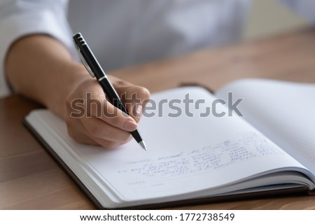 Crop close up of female nurse handwrite hospital patient anamnesis in medical journal at workplace, woman doctor or physician make notes fill clinic client information in paper book register