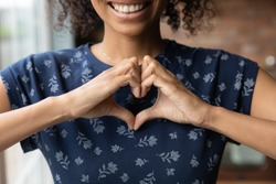 Crop close up of happy African American woman feel grateful thankful show heart sign spread love and care. Smiling biracial female volunteer make hand gesture support ill sick people patients.