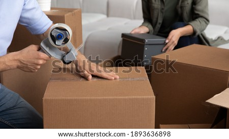 Crop close up of happy couple pack wrap boxes with adhesive scotch moving to new home together. Man and woman renters seal packages with tape dispenser on relocation day. Rent, delivery concept. Stock photo ©