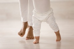 Crop close up of little African American baby toddler learn walking at home holding mom hands. Caring mother teach small biracial daughter child kid, make first steps together. Parenthood concept.