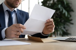 Crop close up of male employer sit at office desk hold paperwork correspondence analyzing report or statistics, Caucasian businessman read consider postal paper document or post letter at workplace
