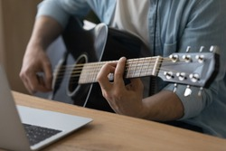 Crop close up of male music coach or tutor play guitar have online video lesson on laptop at home studio. Man artist or singer use musical instrument record new song or single. Hobby concept.
