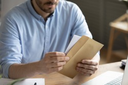 Crop close up of man sit at desk open envelope with paper letter or correspondence at office. Male worker get postal paperwork or notice notification at workplace, receive message or invitation.