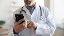 Crop close up of mature male doctor in white uniform hold smartphone browse internet in clinic. Senior man GP look at cellphone screen, use modern cell gadget consulting patient online in hospital.
