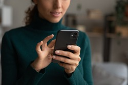 Crop close up of millennial female look at smartphone screen browse surf wireless internet on modern gadget. Young Caucasian woman hold use cellphone device text or message online on cell.