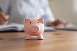 Crop close up of piggy bank on wooden table in hospital or private clinic for monetary donation, piggybank on desk for voluntary money contribution or charity for patient need care, volunteer concept