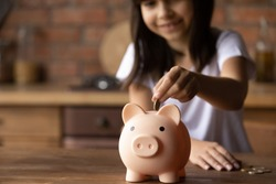 Crop close up of provident economical small girl kid put money into piggybank saving for future needs. Happy smart little 9s teen child make donation contribution in piggy bank. Investment concept.