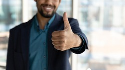 Crop close up of smiling African American businessman show thumb up recommend good quality service. Happy ethnic man give recommendation to company or training course. Employment concept.