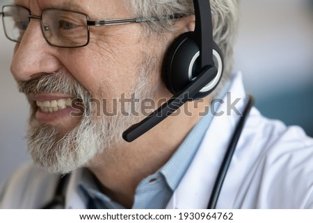 Crop close up of smiling senior Caucasian male doctor wear headphones have webcam virtual consultation with patient in hospital. Happy mature man GP in earphones talk speak on video call in clinic.