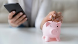 Crop close up of woman put coin in piggy bank save money for future, use financial app on cellphone, female or housewife manage household finances or expenditures, account investment on smartphone
