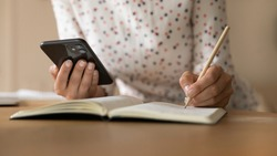 Crop close up of woman sit at desk watch webinar on smartphone make notes in stationery notepad. Female student study online take distant course on web, use cellphone write handwrite in notebook.